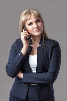 Bedrijfs vrouw in blauw kostuum dat op de telefoon spreekt.