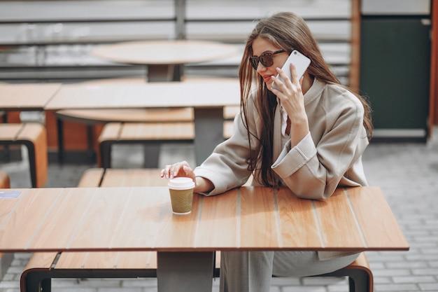 Bedrijfs vrouw in een koffie die coffe, gebruikend telefoon drinkt