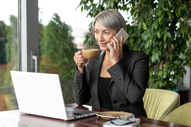 Bedrijfs vrouw in onderbreking die over telefoon spreekt