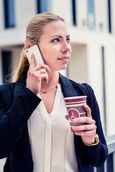 Bedrijfs vrouw met telefoon en koffie