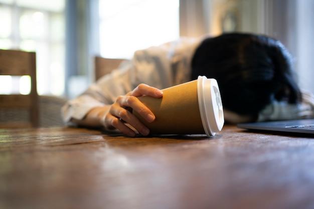 Bedrijfs vrouwelijke holdingskoffiekop en het voelen uitgeput