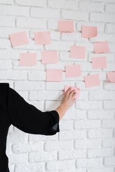 Bedrijfs vrouwelijke plakkende kleverige nota's over muur