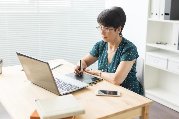 Bedrijfs-, webdesign en grafische kunst concept - vrouw van middelbare leeftijd met behulp van pan schets apparaat.