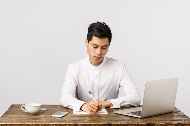 Bedrijfs-, werk- en interviewconcept. drukke serieuze knappe, jonge aziatische man zit bureau in kantoor koffie drinken, rapport schrijven, documenten bestuderen, laptop gebruiken, smartphone,