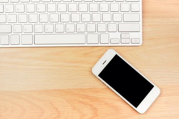 Bedrijfs werkende slimme telefoonlaptop op bruine houten lijst. bovenaanzicht