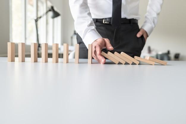 Bedrijfsadviseur die vallende domino's met zijn hand in een conceptueel beeld tegenhoudt.