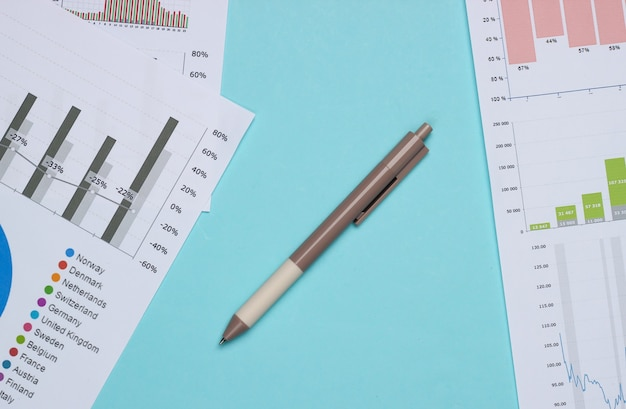Bedrijfsanalyse. financiële analyse. pen met grafieken en diagrammen op blauwe achtergrond. bovenaanzicht