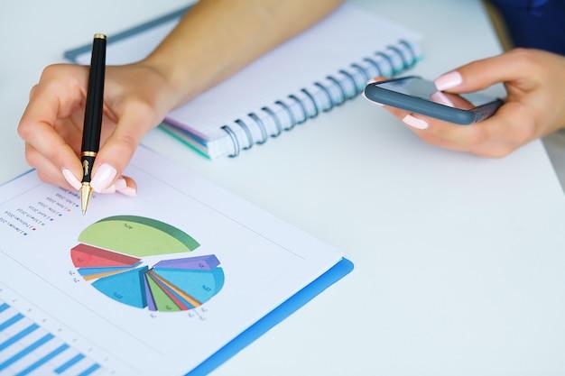 Bedrijfsanalyse - mens die met financiële gegevensgrafieken op kantoor werkt