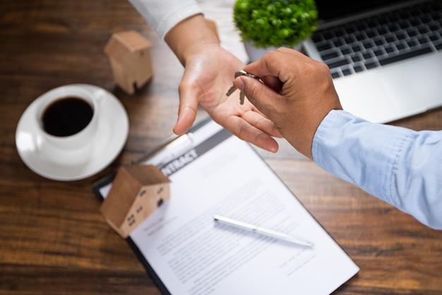 Bedrijfsbankagentschap geeft sleutel van huis en voorstel aan klant, huisvestingslening in goedkope rente voor het kopen van huis en flat afgewerkt contract van onroerend goedconcept.