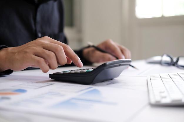 Bedrijfsboekhoudconcept, zakenman met rekenmachine met computerlaptop, budget en leningpapier op kantoor.