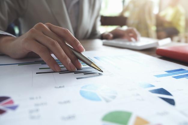 Bedrijfsboekhoudingsconcept, bedrijfsmensenpen die grafiek richten en calculator gebruiken aan het berekenen van begroting en leningsdocument in bureau.