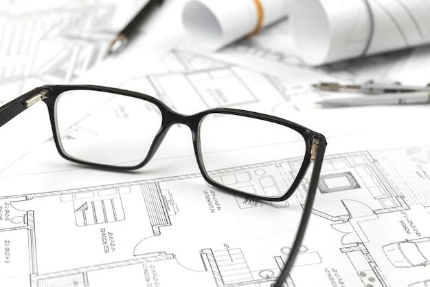 Bedrijfsbouwconcept. werken op kantoor met blauwdrukken, werkplek met architectonisch plan en papieren blauwdrukken. achtergrondfoto bouwproject