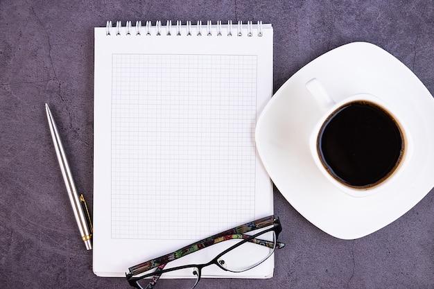 Bedrijfsbureau met kantoorbenodigdheden, notitieboekje, pen, bloem, bril op donker. plat ontwerp, uitzicht vanaf de bovenkant. concept.