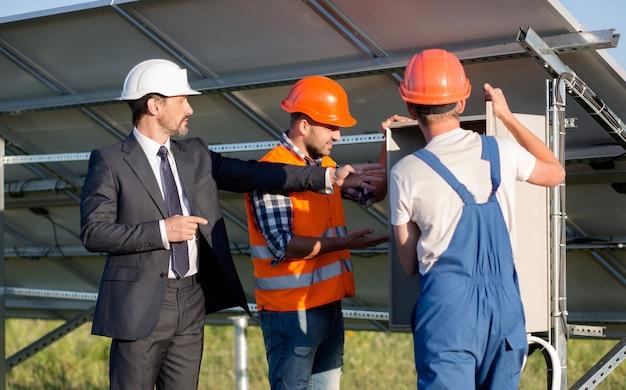 Bedrijfscliënt en twee werknemers die elektrodoos bekijken.