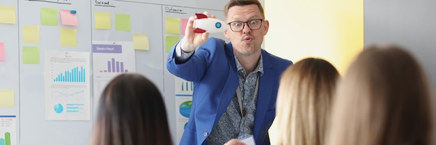 Bedrijfscoach die een bril draagt die speelgoedraket laat zien aan luisteraars in het publiek