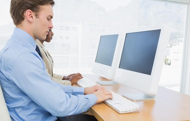 Bedrijfscollega's die computers gebruiken bij bureau