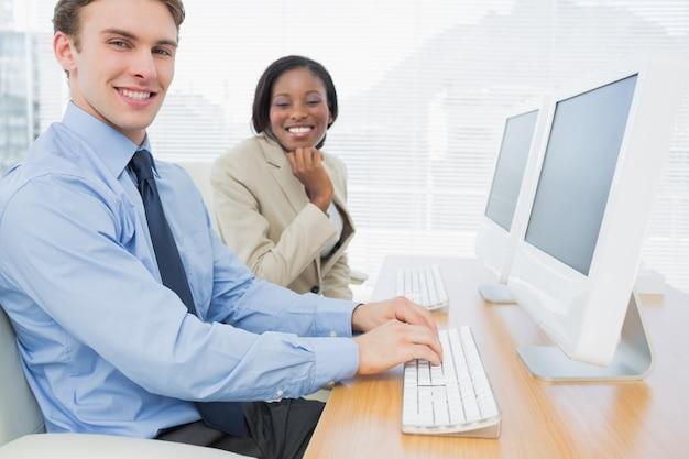 Bedrijfscollega's die computers met behulp van bij bureau