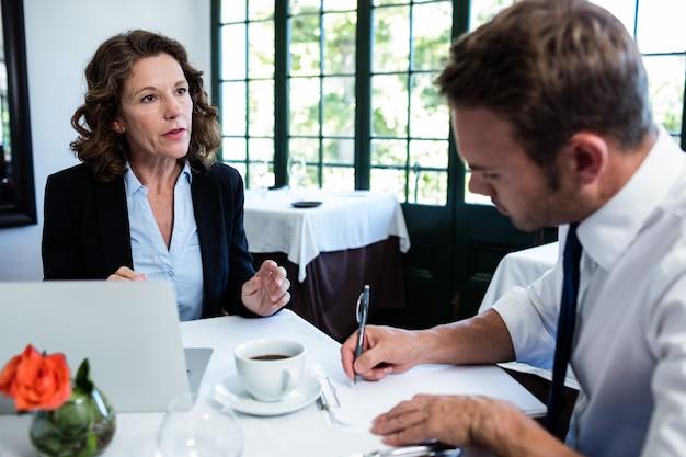 Bedrijfscollega's die en nota's bespreken bespreken terwijl het hebben van een vergadering