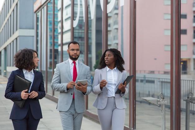 Bedrijfscollega's die en op straat lopen spreken