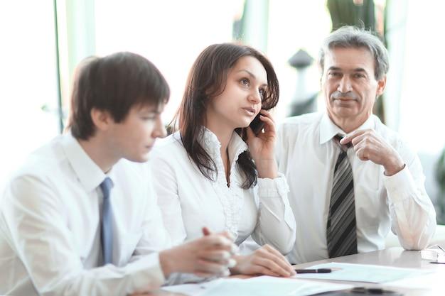 Bedrijfscollega's die financiële statistieken analyseren die aan een bureau op kantoor zitten.