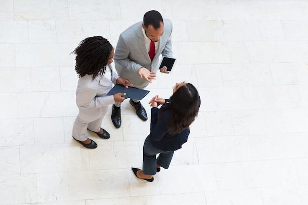 Bedrijfscollega's die in zaal samenkomen en project bespreken