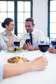 Bedrijfscollega's die mobiele telefoon tijdens bedrijfslunchvergadering bekijken