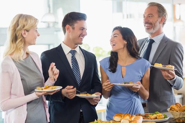 Bedrijfscollega's die op elkaar inwerken terwijl ze zichzelf bedienen tijdens lunchbuffet