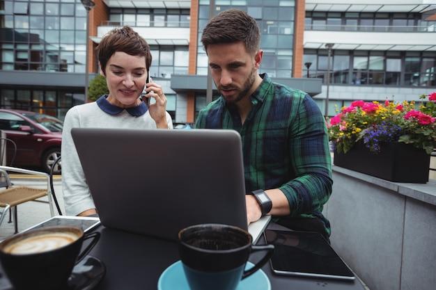 Bedrijfscollega's die terwijl het hebben van koffie in cafetaria werken