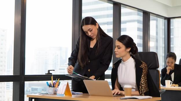 Bedrijfscollega's die terwijl het zitten bij bureau bespreken