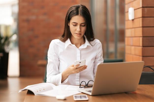 Bedrijfscommunicatie. kaukasische zakenvrouw praten op mobiele telefoon werken op laptop in moderne kantoor.