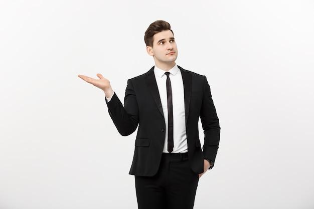Bedrijfsconcept: aantrekkelijke knappe zakenman toont hand aan kant. kopieer de ruimte op een witte achtergrond