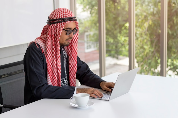 Bedrijfsconcept; arabische zakenman die met computer voor mededeling in modern bureau werkt