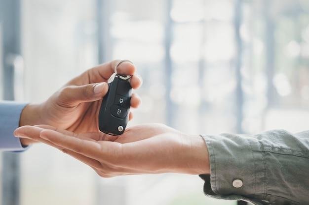 Bedrijfsconcept, autoverzekering, auto verkopen en kopen, autofinanciering, autosleutel voor voertuigverkoopovereenkomst. nieuwe huiseigenaren nemen sleutels af van mannelijke verkopers.