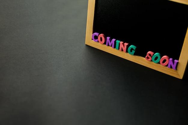 Bedrijfsconcept - blackboard met inscriptie binnenkort op een zwarte tafel.