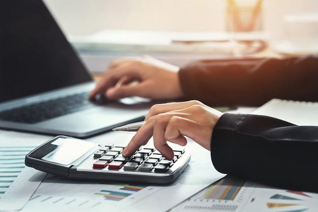 Bedrijfsconcept boekhouding financiën. accountant met behulp van calculator voor berekenen met laptop werken in office