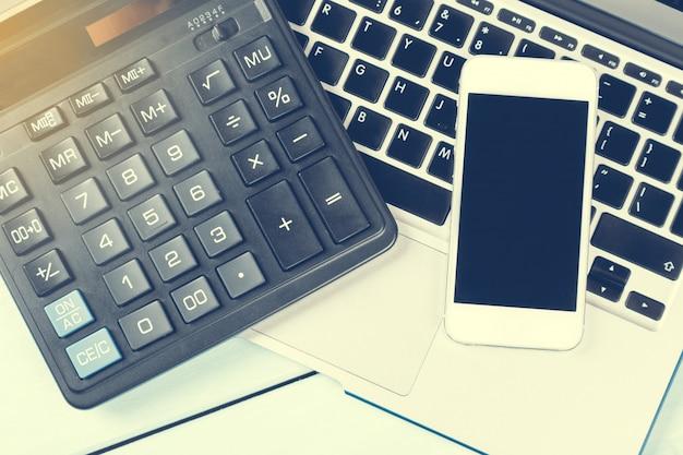 Bedrijfsconcept. bureau met laptop, rekenmachine, moderne telefoon en laptop op houten tafel