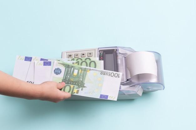 Bedrijfsconcept. close-up van de hand van een kind met een kopie van 100 eurobankbiljetten boven de kassa op een blauwe achtergrond, bovenaanzicht, kopieerruimte. online winkelconcept.