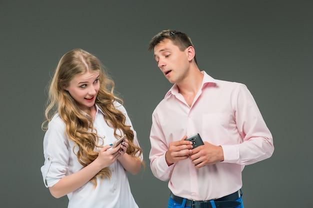 Bedrijfsconcept. de twee jonge collega's met mobiele telefoons op grijze achtergrond