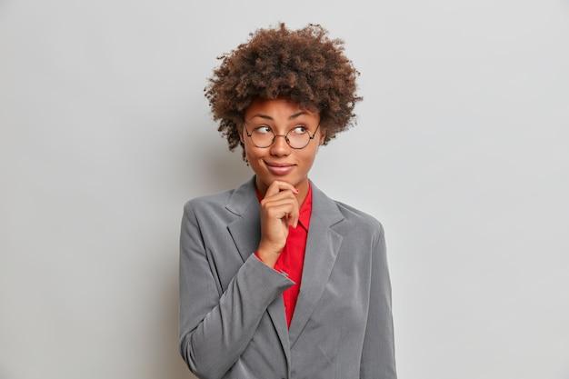 Bedrijfsconcept. doordachte, donkere vrouwelijke manager houdt de kin vast en kijkt peinzend weg en bedenkt een geweldig plan