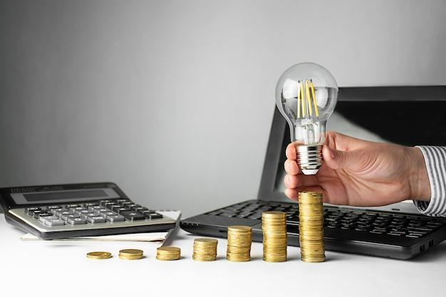 Bedrijfsconcept. een hand houdt een lamp over munten op een licht tafel. zakelijke ideeën, brainstormen. herstel en bedrijfsgroei. kopieer ruimte