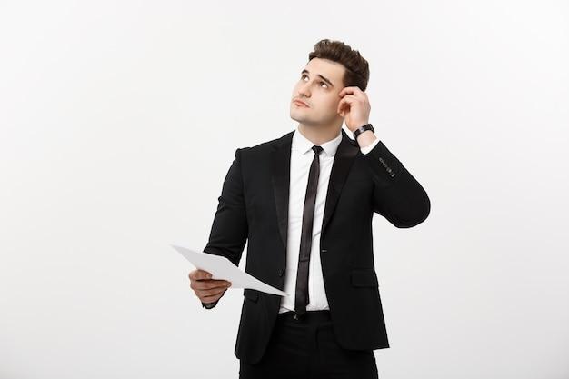 Bedrijfsconcept: gefocuste knappe zakenman die denkt aan jaarlijks bedrijfsrapport, inkomsten of document