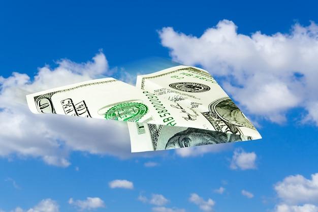 Bedrijfsconcept. geld vliegtuig over blauwe hemel