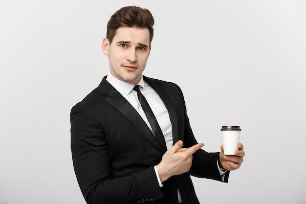 Bedrijfsconcept: halflange foto van een knappe zakenman in een pak die een kopje koffie vasthoudt en ernaar wijst met zijn vinger