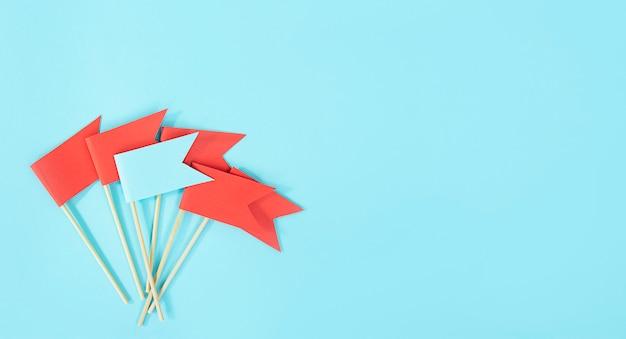 Bedrijfsconcept. het doel bereiken. een blauwe vlag onderscheidt zich van de rode vlaggen op een blauwe tafel. anders zijn. kopieer ruimte.