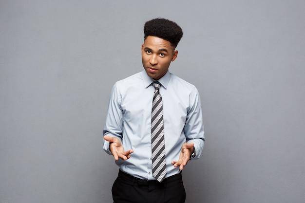 Bedrijfsconcept - het zelfverzekerde vrolijke jonge afrikaanse amerikaanse tonen dient voor hem met een teleurgestelde uitdrukking over grijze muur in.