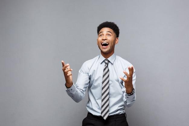Bedrijfsconcept - het zelfverzekerde vrolijke jonge afrikaanse amerikaanse tonen dient voor hem met verrassende uitdrukking over grijze muur in.
