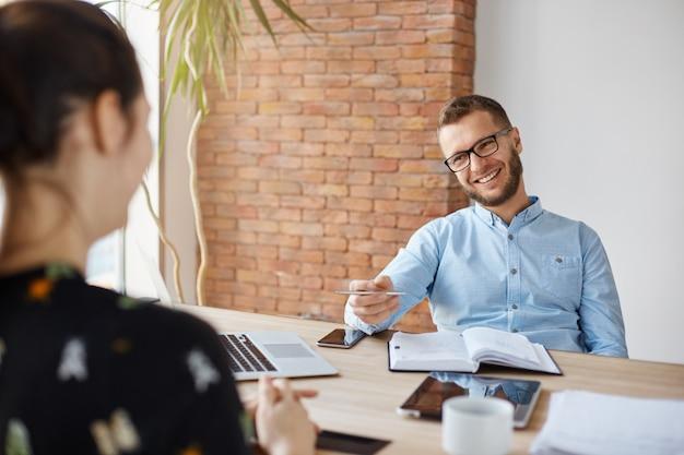 Bedrijfsconcept. jonge donkerharige vrouw zit voor volwassen vrolijke officemanager op sollicitatiegesprek, met ontspannen praten over haar ervaring en studie