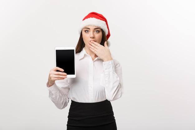 Bedrijfsconcept - jonge kaukasische bedrijfsvrouw in kerstthema die digitale tablet met verrassende gelaatsuitdrukking toont.