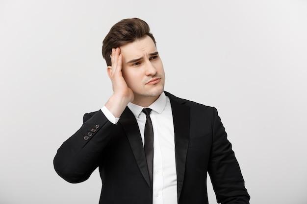 Bedrijfsconcept jonge zakenman met hand in hand op het hoofd met hoofdpijn gezichtsuitdrukking geïsoleerd...