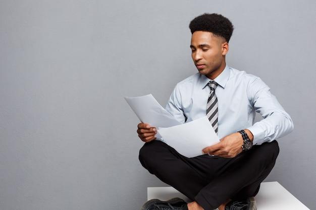 Bedrijfsconcept - knappe jonge professionele afro-amerikaanse zakenman ernstig papierwerk lezen.